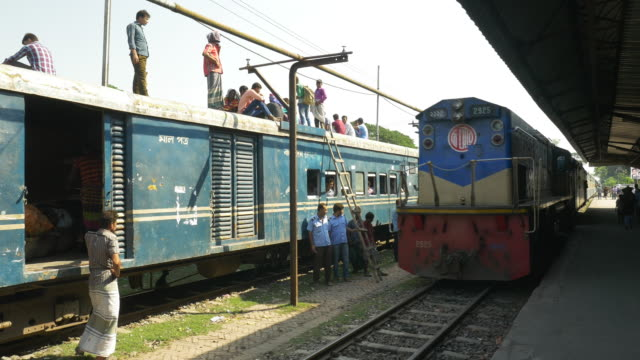 A diesel passenger train with packed carriages arrives at a small station in Northern Bangladesh