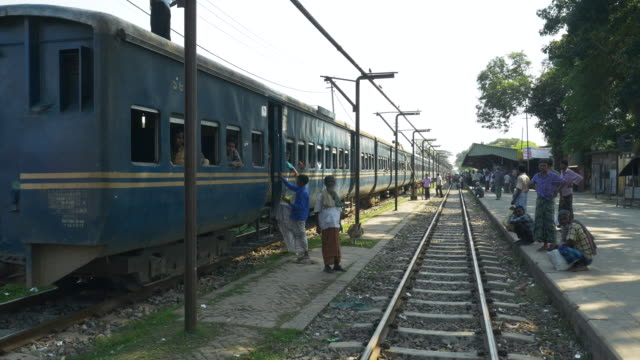 A diesel passenger train with packed carriages idles in a station in Northern Bangladesh before beginning a long journey to Dhaka