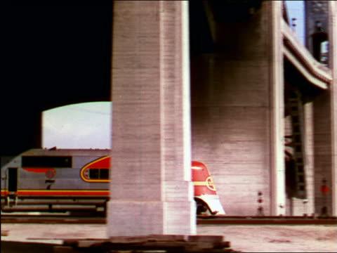 1949 pan diesel train moving under bridge / industrial - 1949 stock-videos und b-roll-filmmaterial