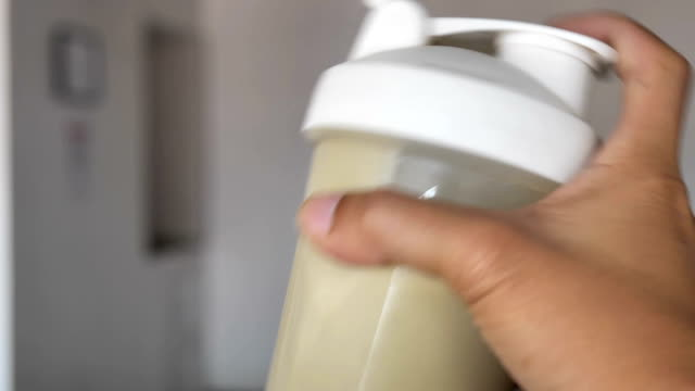 diet shake powder gets mixed with water in a shaker. - proteina video stock e b–roll