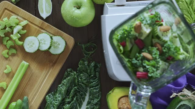 diets concept: directly below panning view shot of woman hands cutting vegetables for detox smoothie. cutting board and blender on kitchen table - crucifers stock videos & royalty-free footage