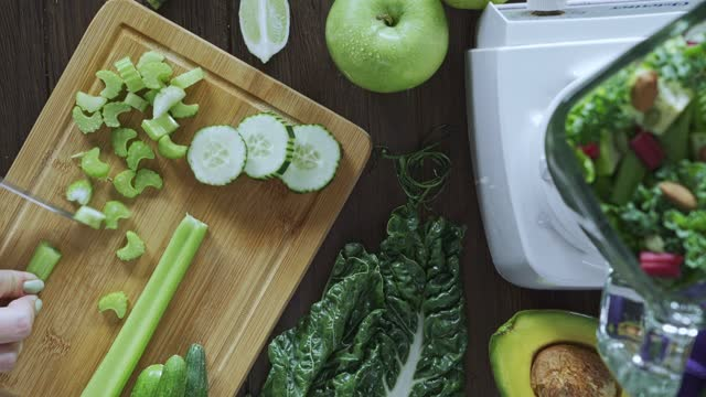 diets concept: directly below panning view shot of woman hands cutting vegetables for detox smoothie. cutting board and blender on kitchen table - celery stock videos & royalty-free footage