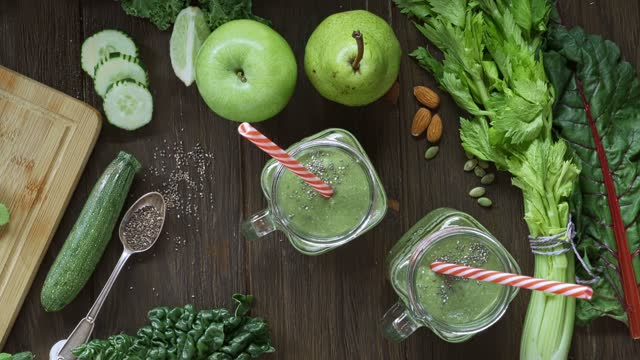 diets concept: directly below shot of woman hands placing drinking straws into mason jars of detox smoothie on rustic kitchen table - celery stock videos & royalty-free footage