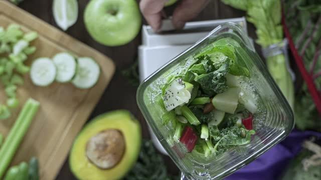 concetto di dieta: slow motion di direttamente sotto colpo di frullatore mescolando verdure e frutta per frullato disintossicante. miscelazione di tagliere e frullatore sul tavolo da cucina - antiossidante video stock e b–roll