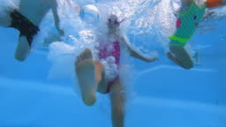 Different aged children jumping into an outdoor swimming pool