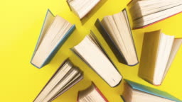 Different books appear on yellow background - Stop motion