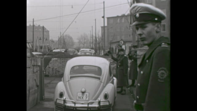 Different border crossings at the Berlin Wall in the american sector soldiers of the GDR army NVA cars passing the border from West to the East...