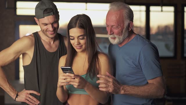 different generations using smartphone in the gym - cross trainer stock videos & royalty-free footage