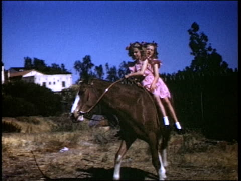 vídeos de stock, filmes e b-roll de different girls wearing dresses ride horse around girls riding horse on july 01 1941 in california - rosa cor