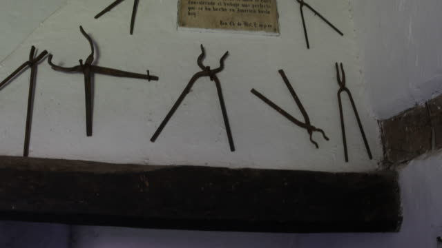 different hand made tools hanging on a wall around a sign in calera de tango chile which were used by german jesuit brothers calera de tango shows... - jesuit stock videos and b-roll footage