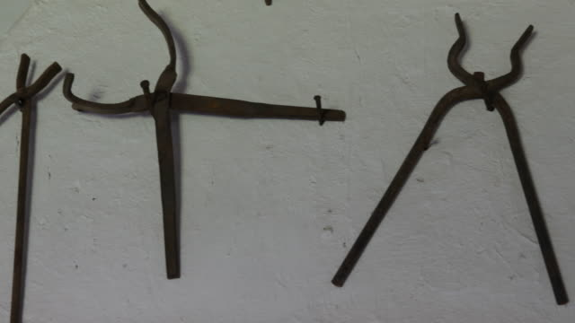 different hand made tools hanging on a wall around a sign in calera de tango chile which were used by german jesuit brothers calera de tango shows... - christian ender stock-videos und b-roll-filmmaterial