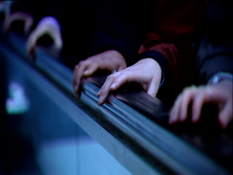 Different people's hands holding onto moving escalator rail in underground station