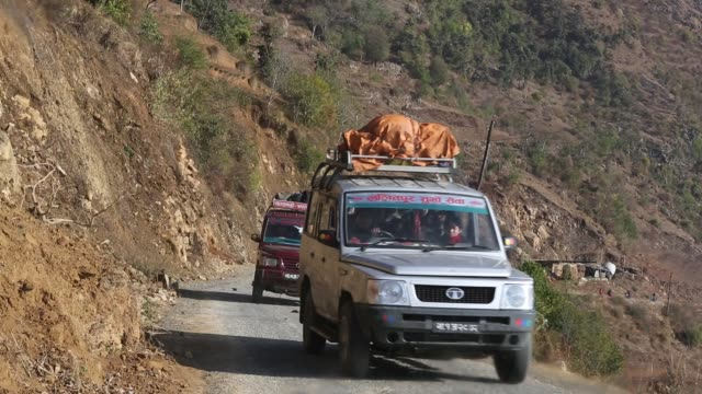 WS of different sorts of vehicles that are passing by on a narrow rocky road in the mountains near Kathmandu Nepal Several people can be seen in the...