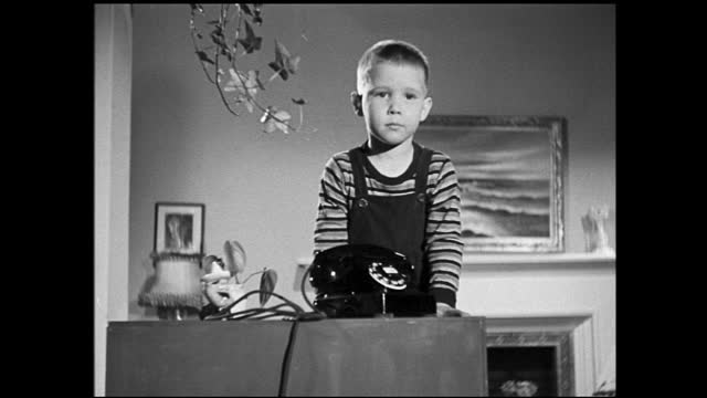 different takes of little boy slowly edging telephone to the edge of desk; telephone falling on the floor - 1940 1949 stock videos & royalty-free footage