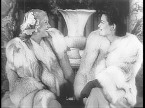vídeos de stock e filmes b-roll de different types of fur coats are laid on a table as they are named by type / a group of models showcase various fur coats / two models in fur coats... - enfeites para a cabeça