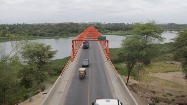 different vehicles are driving on a bridge to cross to the other side of a river in the region of sullana, peru. - puente stock videos & royalty-free footage