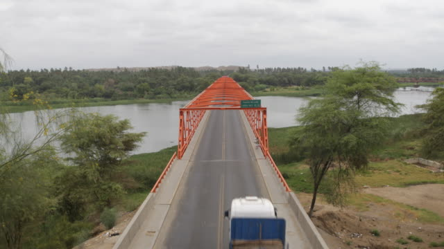 stockvideo's en b-roll-footage met different vehicles are driving on a bridge to cross to the other side of a river in the region of sullana, peru. - puente