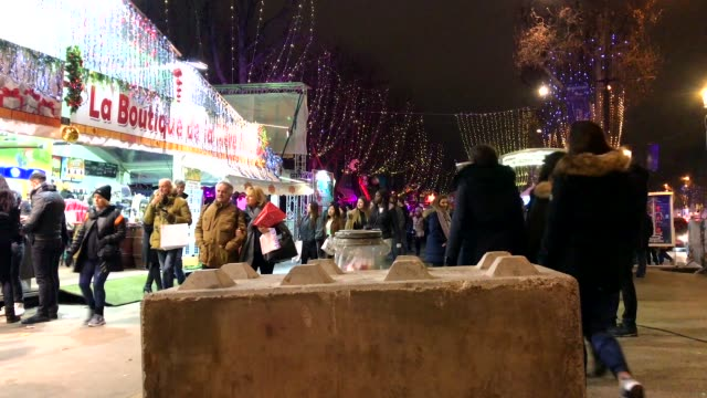 different view of christmas market at night in paris, france at champs elysées. emergency vehicle, anti attack road blocks are visible. - ナイトイン点の映像素材/bロール