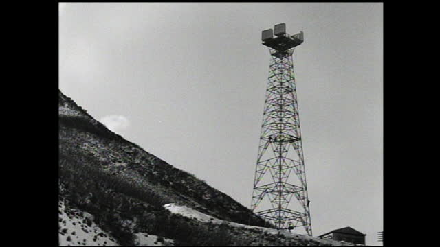 different views of a metal transmitting/relay tower in the hills against the cloudy sky; workers working on the tower - 1940 1949 stock-videos und b-roll-filmmaterial
