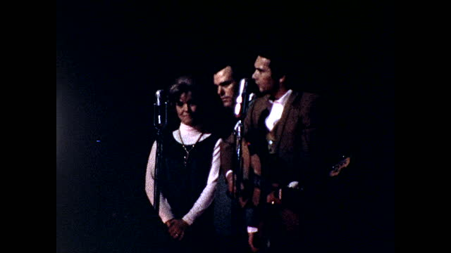 different views of two men and one woman singing on stage behind two microphones, one man playing the guitar at the same time; stable view of... - 1960 1969 stock videos & royalty-free footage