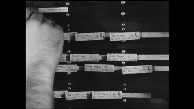 different views of various hands organizing stripboards and slots in the schedule board; lots of labels on the wall - 1940 1949 stock-videos und b-roll-filmmaterial