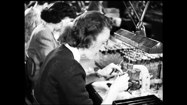 vidéos et rushes de different views of various women assembling light bulbs on the assembly line - 1940 1949