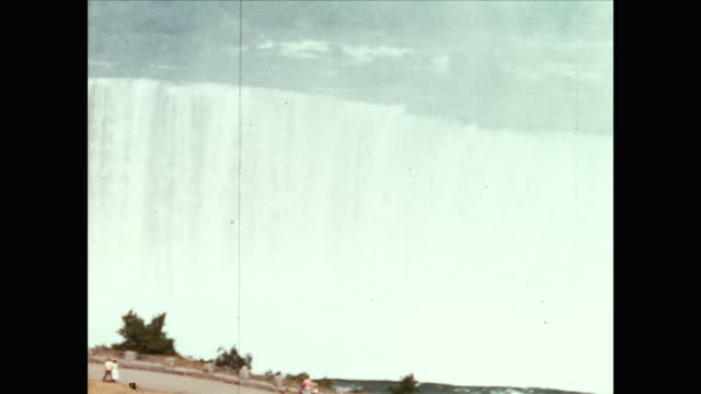 vidéos et rushes de different zoom in views of the niagara waterfall in layers and people watching behind railings; panning view of large rainbow bridge and town behind... - chute d'eau