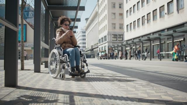 市内中心部の車いすに別様に abled ある若い女の子 - バス停留所点の映像素材/bロール