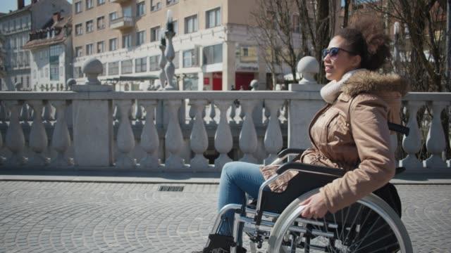 vidéos et rushes de fillette abled différemment sur un fauteuil roulant dans le centre ville - chaise roulante