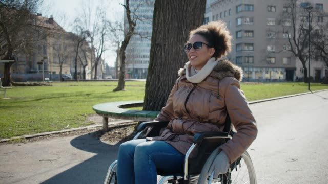 differently abled young girl on a wheelchair in the city park - wheelchair stock videos and b-roll footage