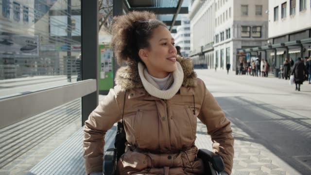 vídeos de stock, filmes e b-roll de abled diferentemente jovem numa cadeira de rodas na paragem de autocarro no centro da cidade - cadeira de rodas equipamento ortopédico