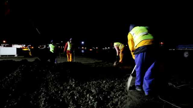 MS Digger and men with shovels digging up the old road on construction site at night, Cape Town, South Africa