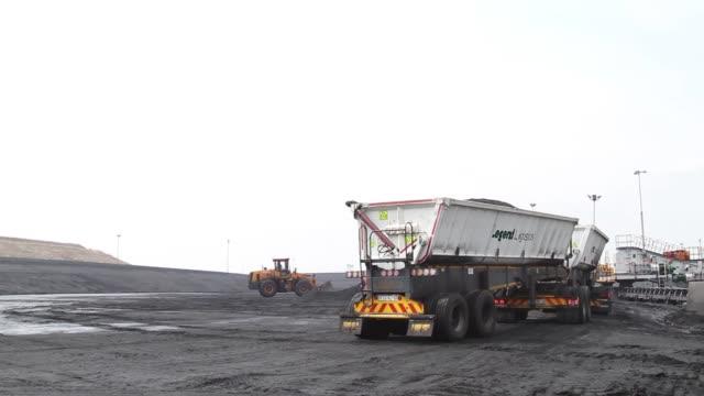 stockvideo's en b-roll-footage met a digger arranges coal stores in the coal yard at the grootvlei power station operated by eskom holdings soc ltd in grootvlei south africa on monday... - bouwvoertuig