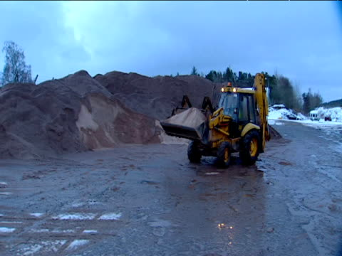 Digger carries road grit in gritter depot Scotland