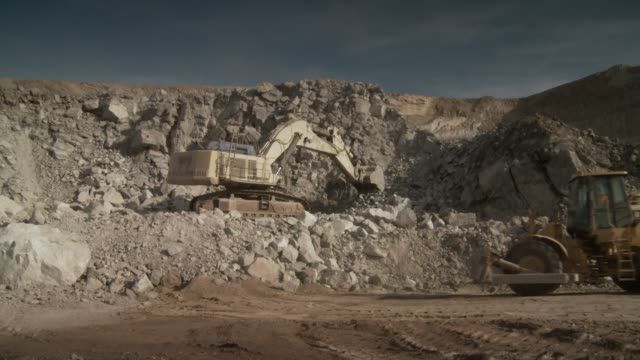 A digger excavates rocks and rubble at a quarry site. Available in HD.