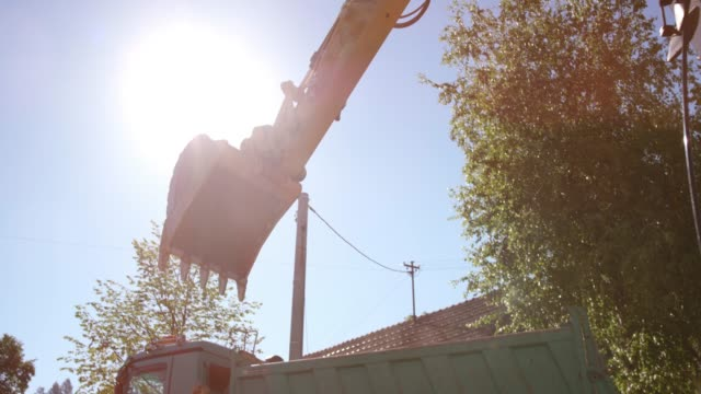 digger filling a truck with construction debris in sunshine - bulldozer stock videos and b-roll footage