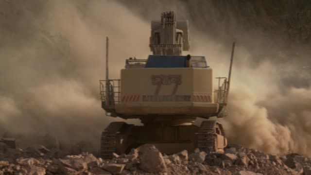 a digger in a quarry rotates through a dust cloud. available in hd. - construction machinery stock videos & royalty-free footage