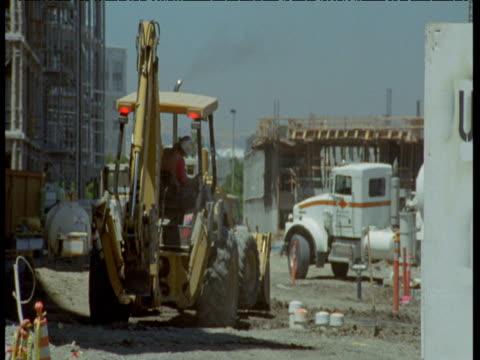 digger manoeuvres on building site, san jose - erektion stock-videos und b-roll-filmmaterial