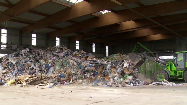 digger moving mixed waste in a recyling center - recycling stock-videos und b-roll-filmmaterial