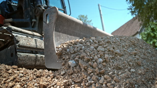 slo mo digger pushing crushed rocks in the sunny construction site - earth mover stock videos & royalty-free footage