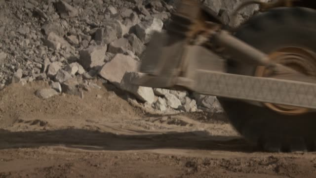 A digger reverses amongst rocks and rubble at a quarry site. Available in HD.