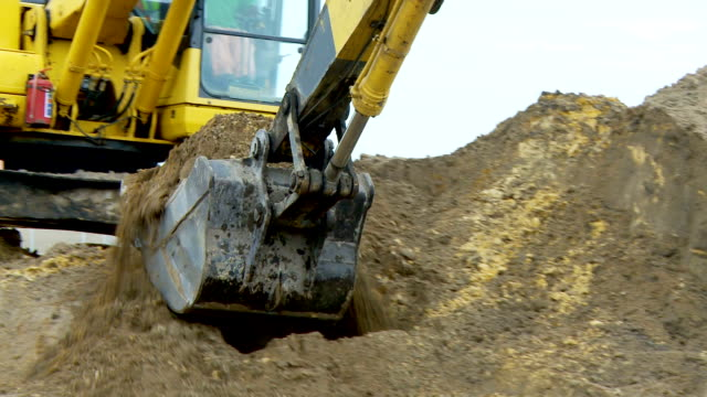 MS Digger shovelling sand into a pit - front view of machine, Cape Town, South Africa