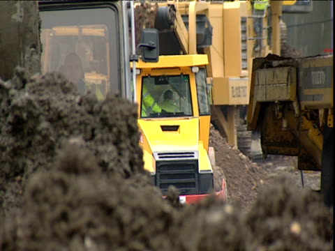 stockvideo's en b-roll-footage met diggers and machinery operate on building site - bouwmachines