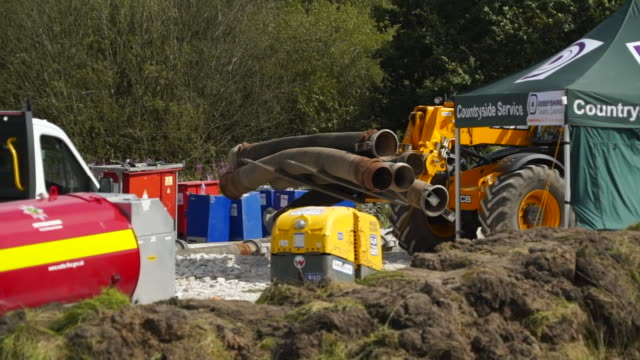 diggers carrying pipes to divert water at the site of the damaged toddbrook reservoir - dam stock videos & royalty-free footage