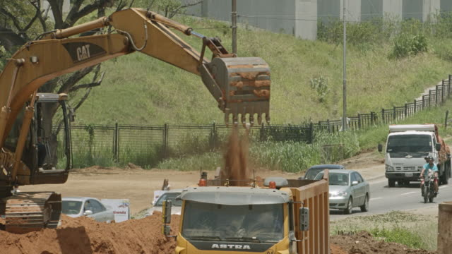 stockvideo's en b-roll-footage met digging excavator in the street - bouwmachines