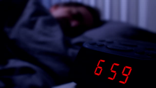 digital alarm clock, man waking up at 7am. - ora di andare a letto video stock e b–roll