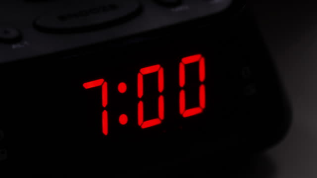 Digital alarm clock, time fro 6.59 to 7.00.