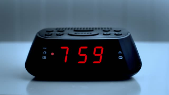 digital alarm clock, time from 7.59 to 8.00. - digital clock stock videos & royalty-free footage