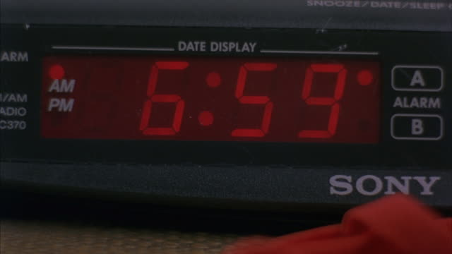 A digital clock radio-alarm changes time from 6:59 a.m to 7:00.