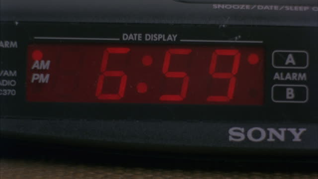 a digital clock radio-alarm changes time from 6:59 a.m to 7:00. - zahl 7 stock-videos und b-roll-filmmaterial